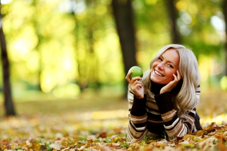 woman with green apple in autumn park 版權商用圖片