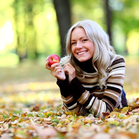 woman with red apple in autumn park photo