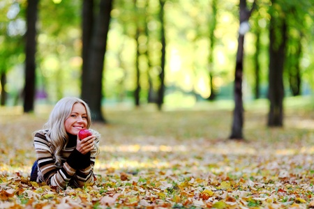 woman with red apple in autumn park Stock Photo - 8585302