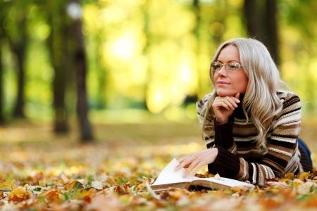 mujer Lee el libro en el Parque de otoño