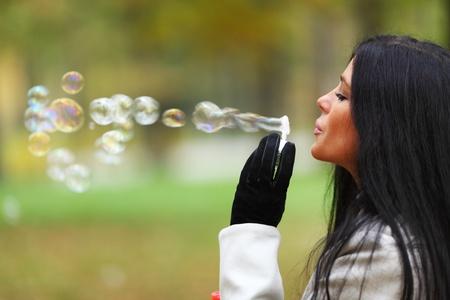 autumn woman blow bubbles portrait in park photo