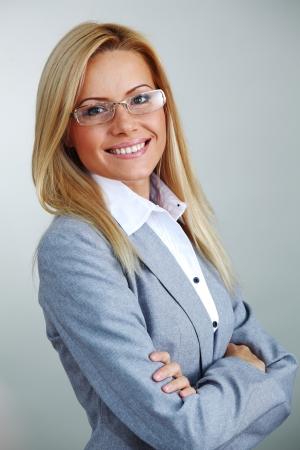 bussines: zakelijke vrouw in glazen op een grijze achtergrond Stockfoto