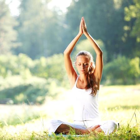 yoga woman on green grass in lotus pose photo