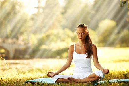 lotus pose: yoga woman on green grass in lotus pose