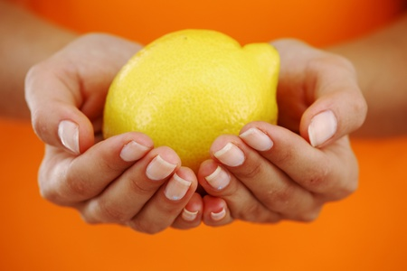 squeezing: lemon in woman hands close up Stock Photo