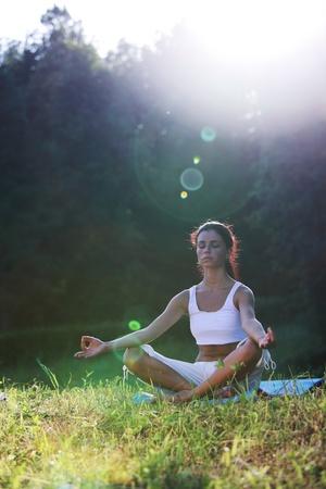 yoga woman on green grass lotus pose in sunrise light Stock Photo - 8587424
