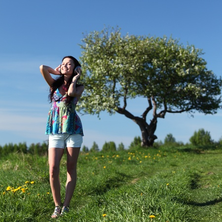 Young woman with headphones listening to music on field Stock Photo - 8586646