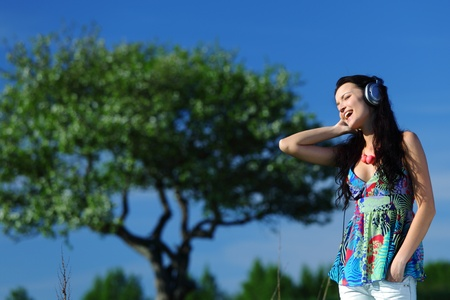 Young woman with headphones listening to music on field Stock Photo - 8585683