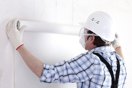 attaching: worker attaching wallpaper to wall
