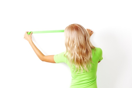 �aucasian: women often with a measuring tape to the wall Stock Photo