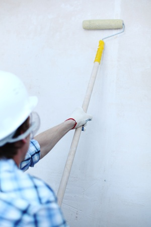 worker spends anchor roller on the wall photo