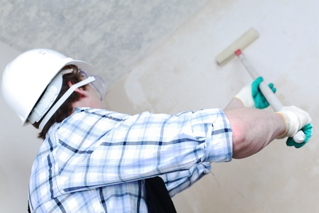 worker spends anchor roller on the wall Stock Photo