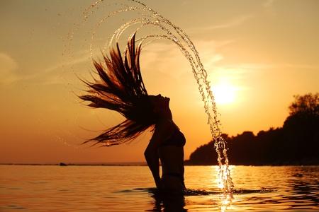 日出光的海洋妇女飞溅头发