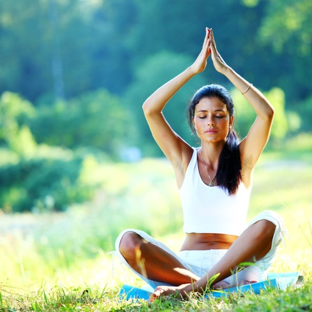 yoga woman on green grass in lotus pose photo