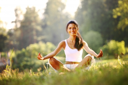lifestyle:  yoga woman on green grass in lotus pose