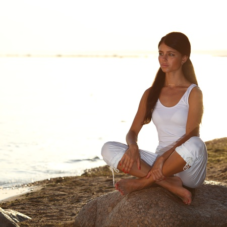 Young woman practicing yoga  near the ocean Stock Photo - 8585250