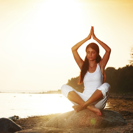 Young woman practicing yoga  near the ocean photo
