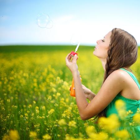 woman start soap bubbles on yellow flower field photo