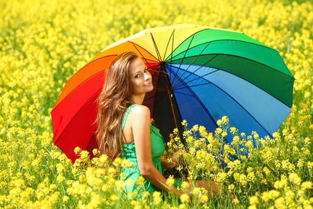 woman under umbrella on yellow flower field