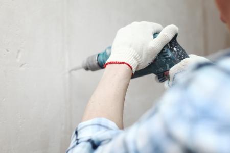 man worker hammer drills wall photo
