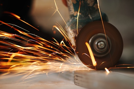 grinder machine: metal sawing close up sparks spray