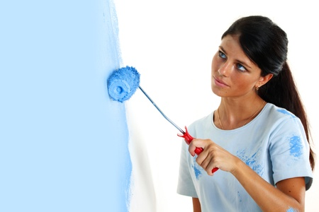 roller in woman hand paint on the wall photo
