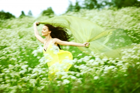 girl run by field fabric in hands fly behind like wings photo