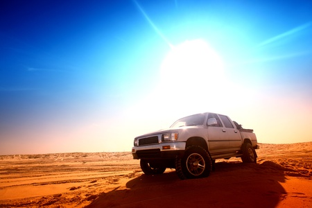 desert road: truck in desert sand and blue sky