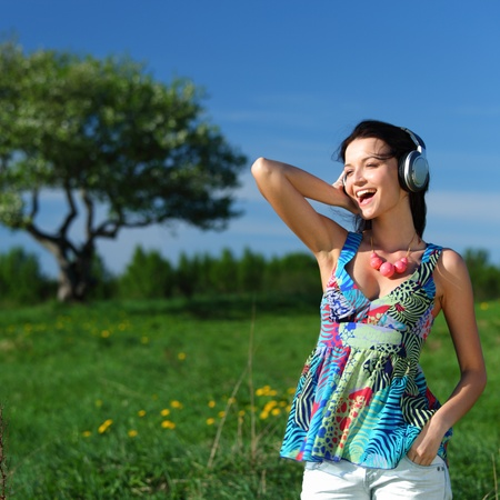 Young woman with headphones listening to music on field Stock Photo - 8743668