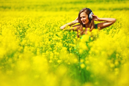 flowering field:  Young woman with headphones listening to music on oilseed flowering field