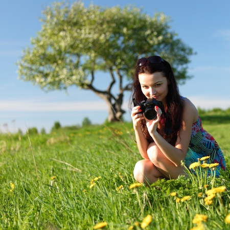 woman photographer on green grass field photo