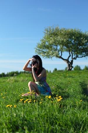 woman photographer on green grass field Stock Photo - 8743901