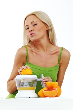 woman squeezes juice by juicer photo