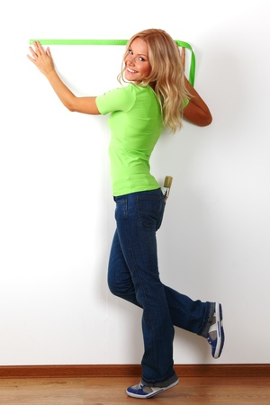 women often with a measuring tape to the wall photo