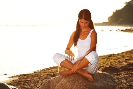 Young woman practicing yoga  near the ocean Stock Photo - 8739766