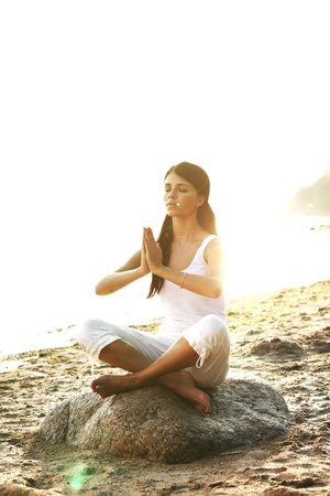 meditating woman: Young woman practicing yoga  near the ocean Stock Photo