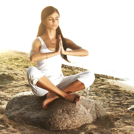 Young woman practicing yoga  near the ocean Stock Photo - 8743766