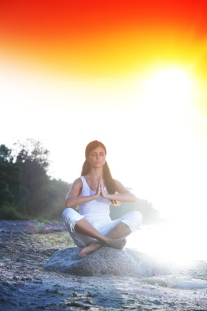 Young woman practicing yoga  near the ocean Stock Photo - 8743765