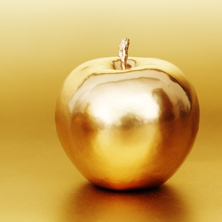 vitamin rich:  gold apple on gold background Stock Photo