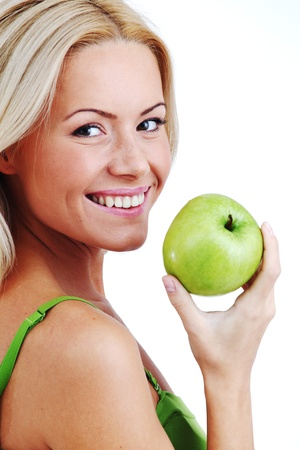 blond woman eat green apple on white photo