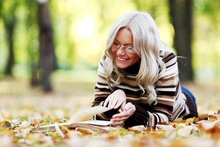 fille pull: femme lire le livre dans le parc automne Banque d'images