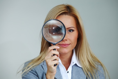 see through: business woman looking through a magnifying glass