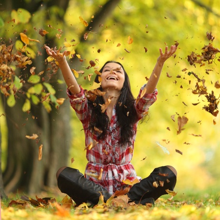 healthy people: woman drop up leaves in autumn park
