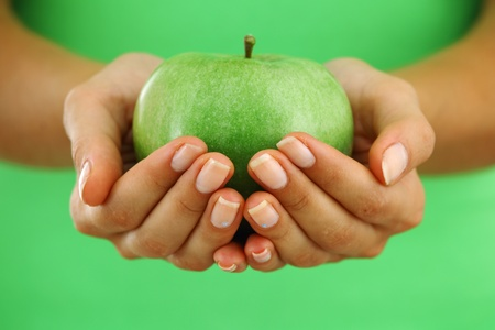 apple in woman hands close up photo