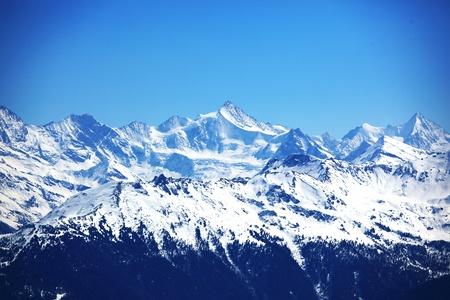 monta�as nevadas: parte superior de las monta�as en el cielo azul Foto de archivo