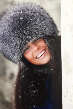 woman in fur hat hide behind column Stock Photo - 8751176