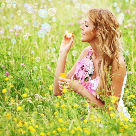 day dreams:  Blonde starts soap bubbles in a green field Stock Photo