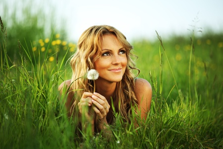 natural love: girl blow on dandelion on green field Stock Photo