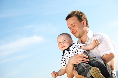 father and son in blue sky photo
