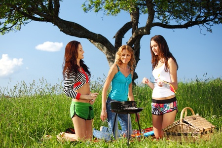 girls burn sausages on barbecue photo